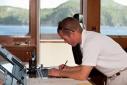 Chief Officer Ferdi Heymann working at the chart table aboard Big Aron