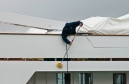 Deckhand cleaning the superstructure aboard a large yacht
