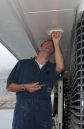 Electrician changing deckhead light bulb aboard MY Solemates