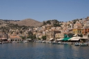 Picturesque houses and shops in Symi harbour, Gialos,  from the sea