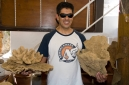 The shop keeper holding examples of sponges found around Symi
